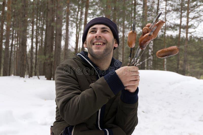 Тучный человек с сосисками округляет его шею, питание низкого качества, проблему тучности стоковая фотография
