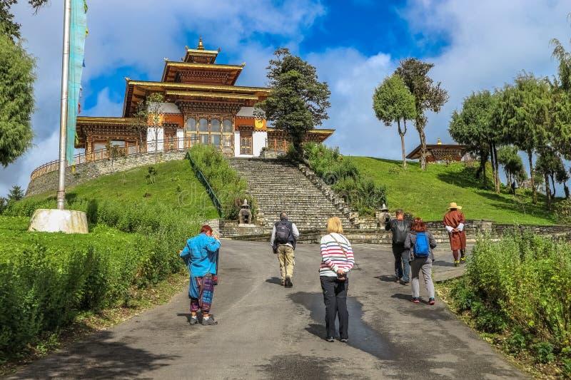 Тхимпху, Бутан - 10-ое сентября 2016: Туристы идя через висок Druk Wangyal Lhakhang, пропуск Dochula, Бутан стоковая фотография