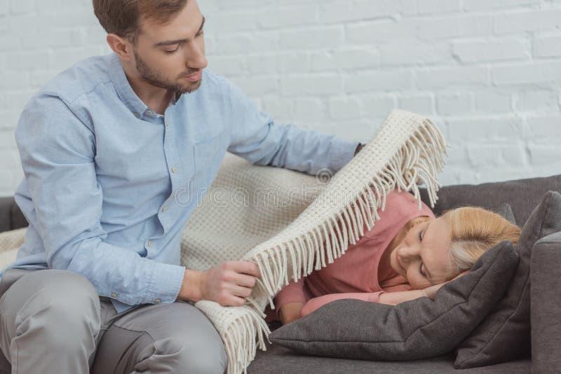 тщательная, который выросли мать заволакивания сына спать на софе стоковые фотографии rf