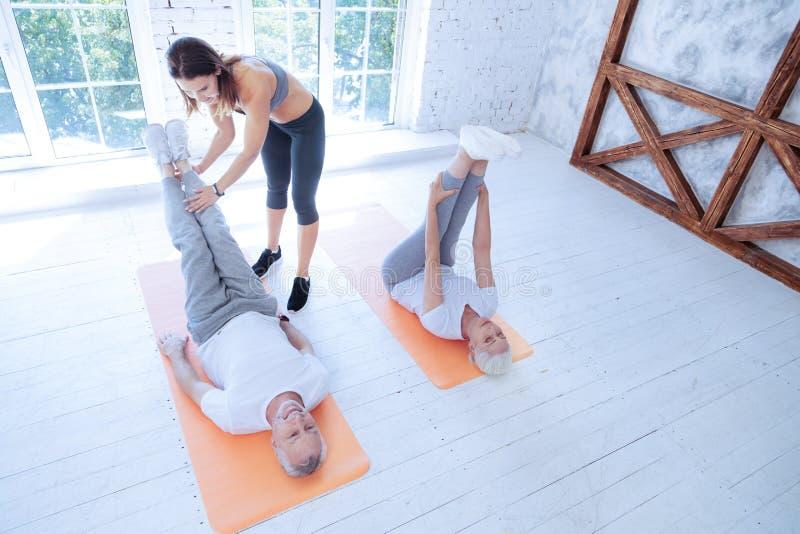 Тщательный тренер фитнеса помогая ее клиенту стоковое фото