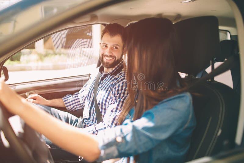 Тщательный управлять Красивые молодые пары сидя на передних сиденьях пассажира и усмехаясь пока женщина управляя автомобилем стоковые изображения rf