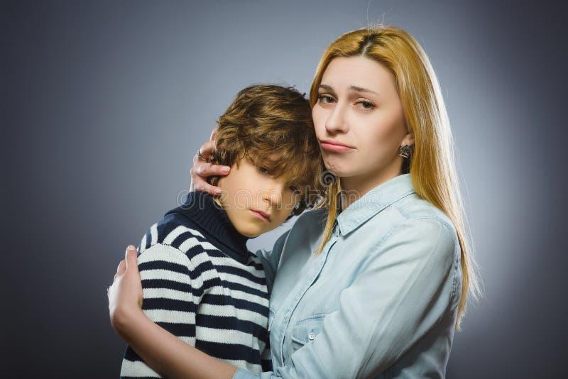 Тщательная мать жалеет сына Изолировано на сером цвете стоковые фото