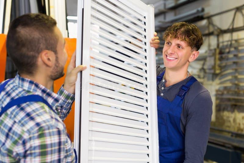 2 тщательных рабочего класса проверяя окна стоковая фотография rf