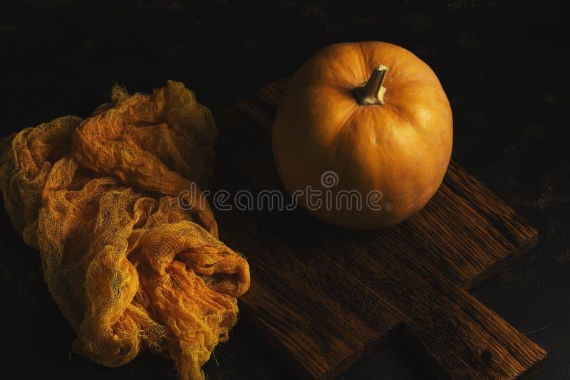 Тыква на старой разделочной доске, оранжевой ткани, темной предпосылке стоковое фото