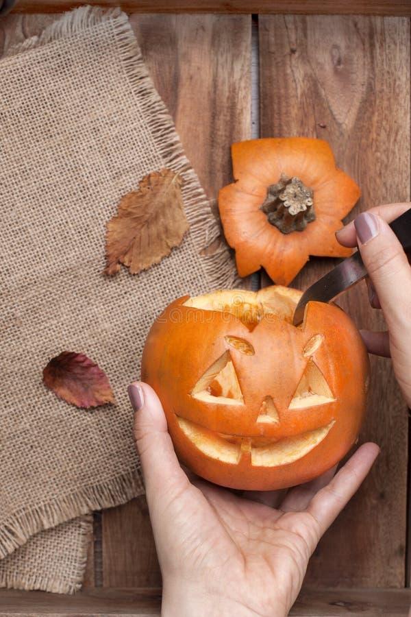 Тыква на хеллоуин в руках ` s женщин, подготавливая на праздник осени Листья и оформление на деревянном столе Взгляд сверху стоковые фотографии rf
