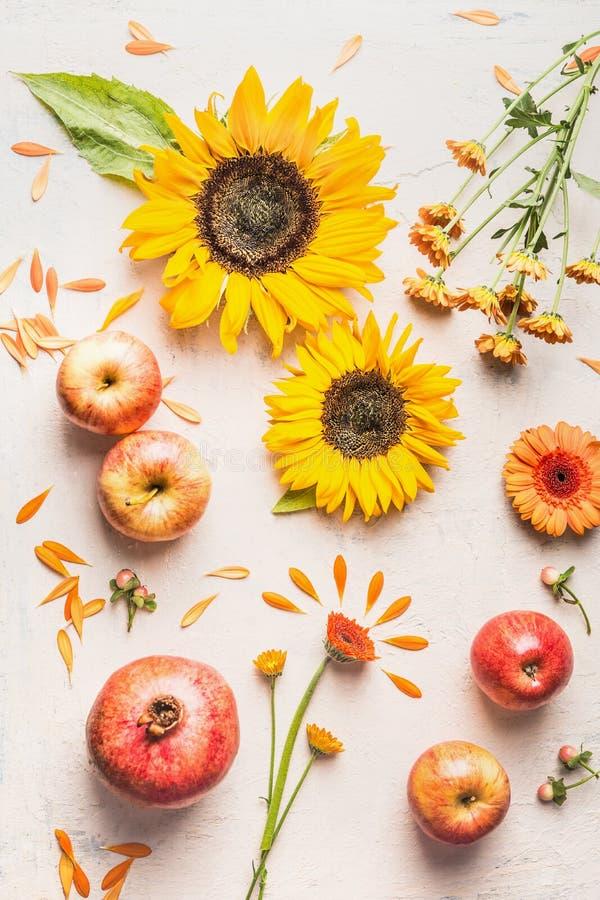 Тыква с яблоками, цветками, гранатовым деревом и солнцецветами на белой таблице, взгляде сверху Составлять плана осени или поздни стоковые изображения
