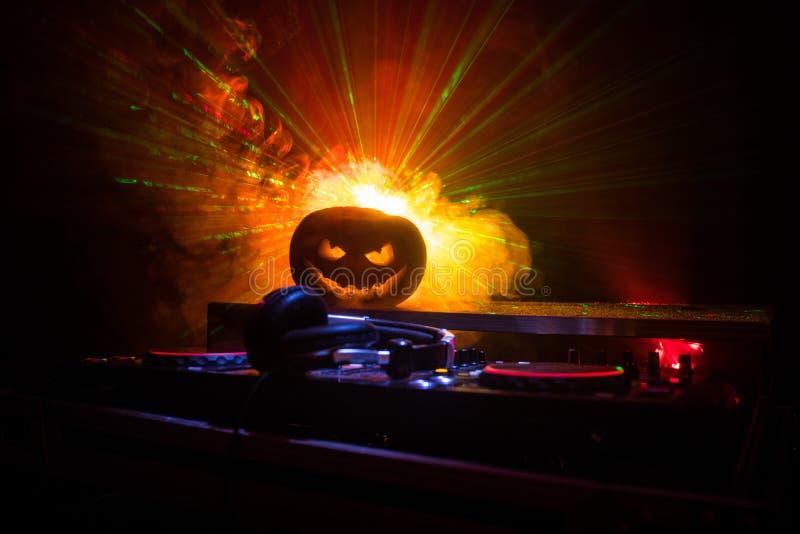 Тыква хеллоуина на таблице dj с наушниками на темной предпосылке с космосом экземпляра Счастливые украшения и музыка фестиваля хе стоковые изображения rf