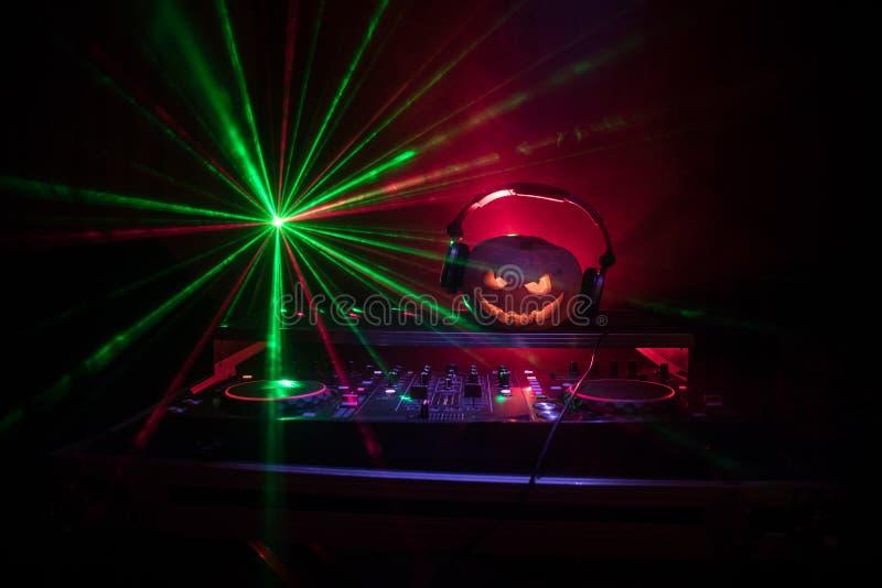 Тыква хеллоуина на таблице dj с наушниками на темной предпосылке с космосом экземпляра Счастливые украшения и музыка фестиваля хе стоковое изображение rf