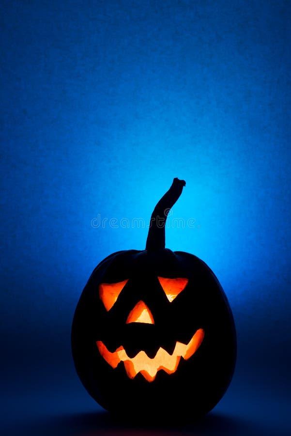 Тыква хеллоуина, силуэт смешной стороны на голубой предпосылке вертикально стоковое изображение
