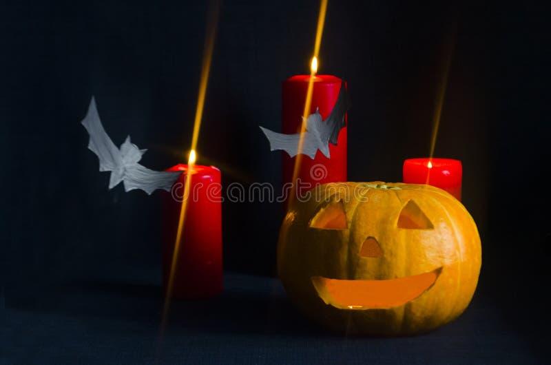 Тыква хеллоуина с горящими свечами, летучими мышами на темной предпосылке стоковое фото rf