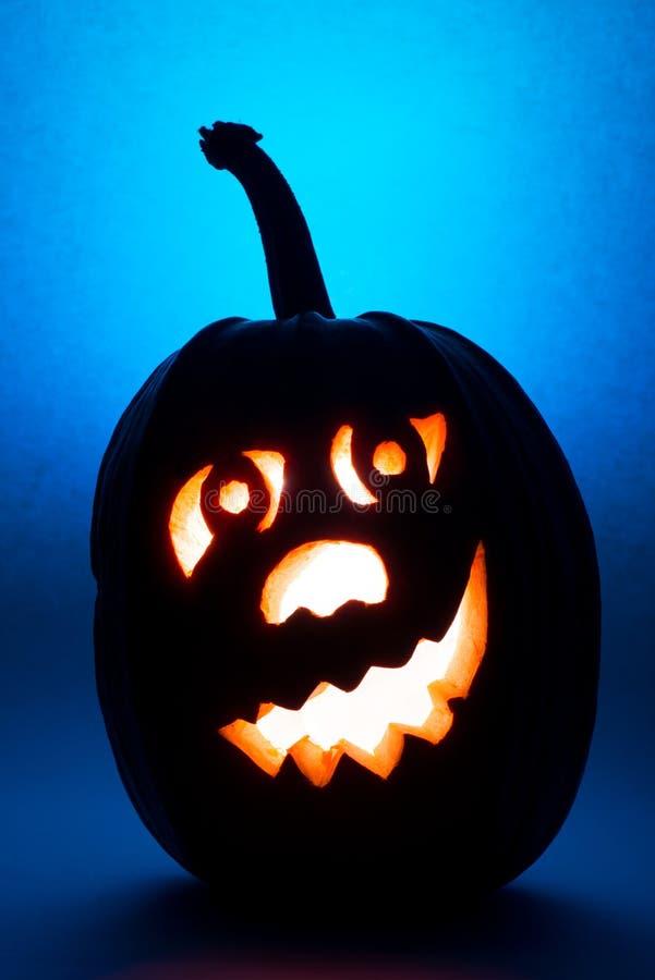 Тыква хеллоуина, силуэт смешной стороны на голубой предпосылке стоковое изображение