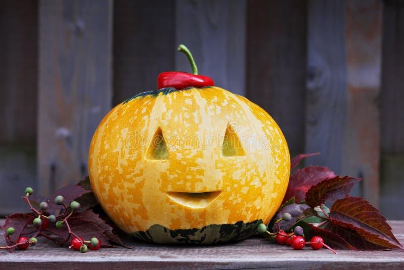 Тыква хеллоуина смешная с улыбкой в листьях осени стоковая фотография