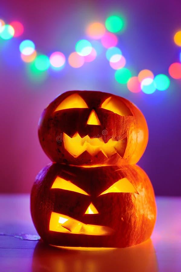 Тыквы хеллоуина возглавляют Джек-o-фонарики с красочными светами на предпосылке стоковое фото