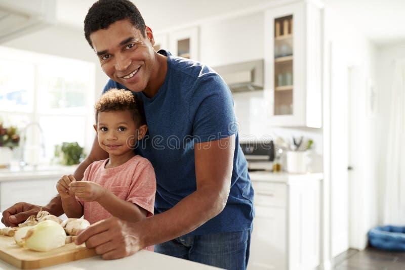 Тысячелетнее положение человека на worktop кухни подготавливая еду с его сыном малыша смотря к камере, концу вверх, передний план стоковое изображение