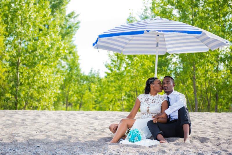 Тысячелетние пары сидя пляжем под зонтиком пока целующ стоковые изображения rf