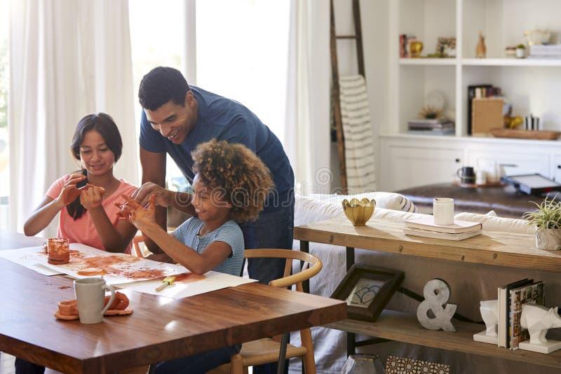 Тысячелетний папа помогая его дочери и ее девушке играя с моделированием глины на таблице столовой стоковые изображения rf