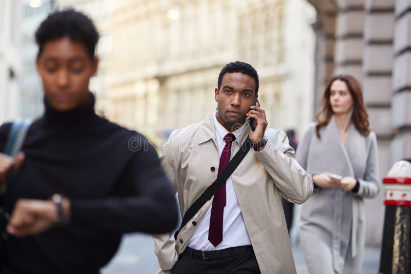 Тысячелетний черный бизнесмен идя в занятую улицу Лондона используя смартфон, выборочный фокус стоковые изображения rf