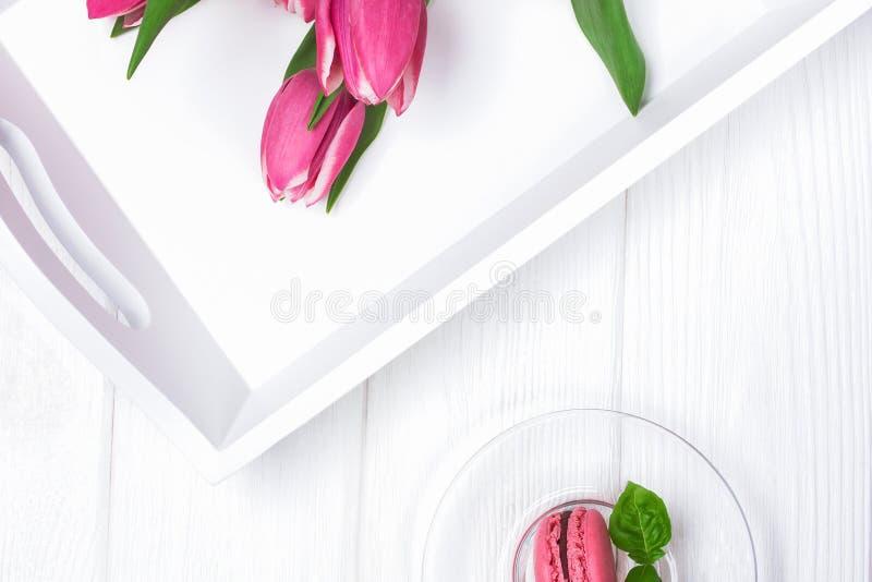 Тюльпаны и macaroon десерта на белой предпосылке Magenta цвет стоковая фотография rf