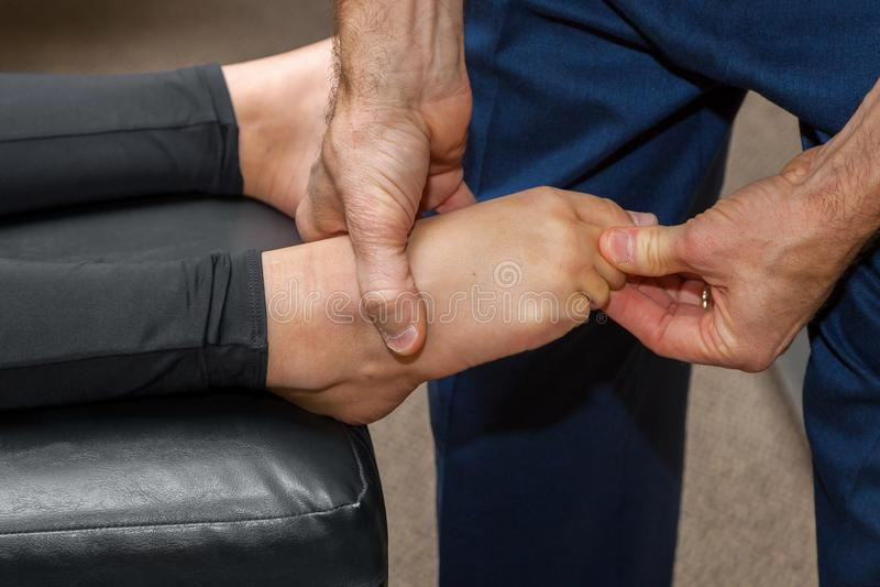 Тяги хиропрактора на пальце ноги девушки для того чтобы отрегулировать ее ногу стоковые изображения rf