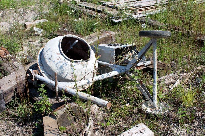 Тяжело - использованный сломанный и частично заржаветый электрический конкретный смеситель сброшенный на строительной площадке стоковые фото