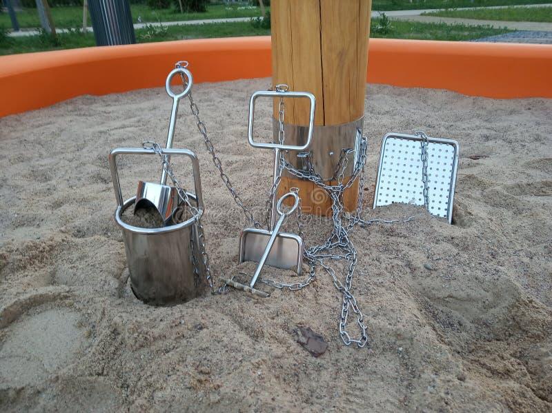Тяжелые игрушки песка детей утюга или металла связанные к столбу цепями в ящике с песком трудное детство, система анти--похищения стоковые изображения rf