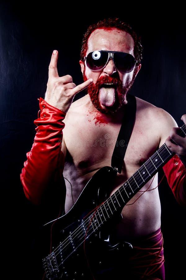 Тяжелый, гитарист с чернотой электрической гитары, нося краска стороны стоковое фото