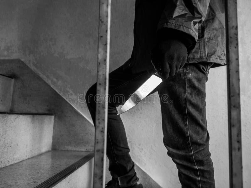 Убийство, человек держа нож в его руке идет вверх по лестницам, концепции угрозой стоковая фотография rf