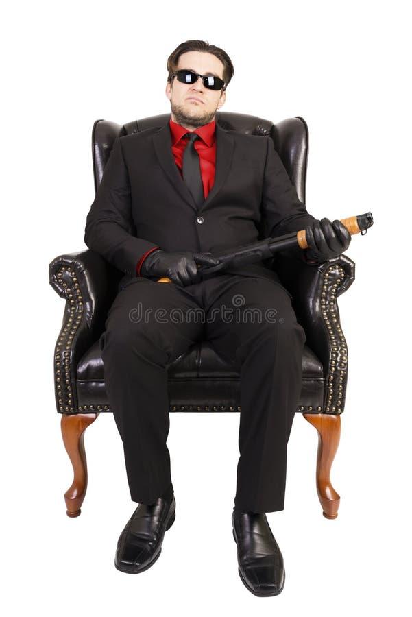 Убийца сидя на стуле стоковое изображение