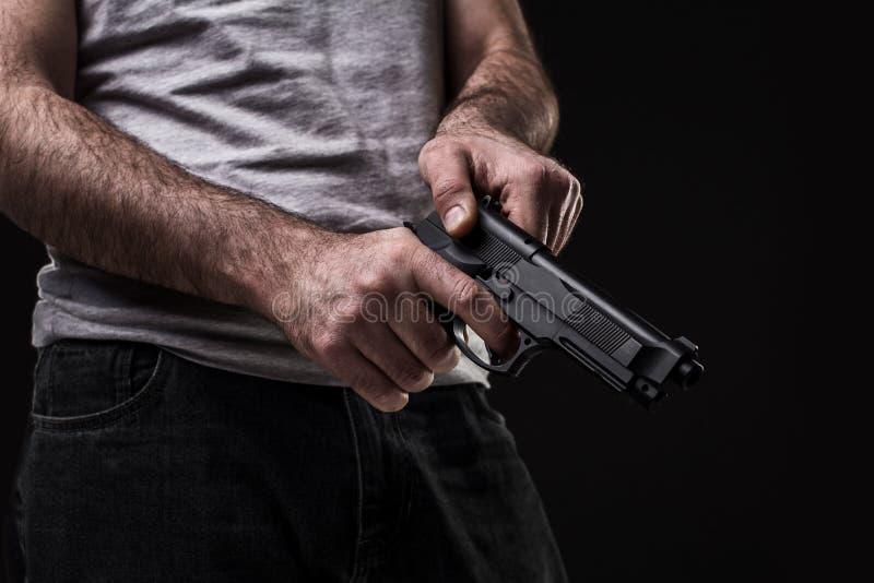Убийца с оружием на черной предпосылке на студии стоковые изображения
