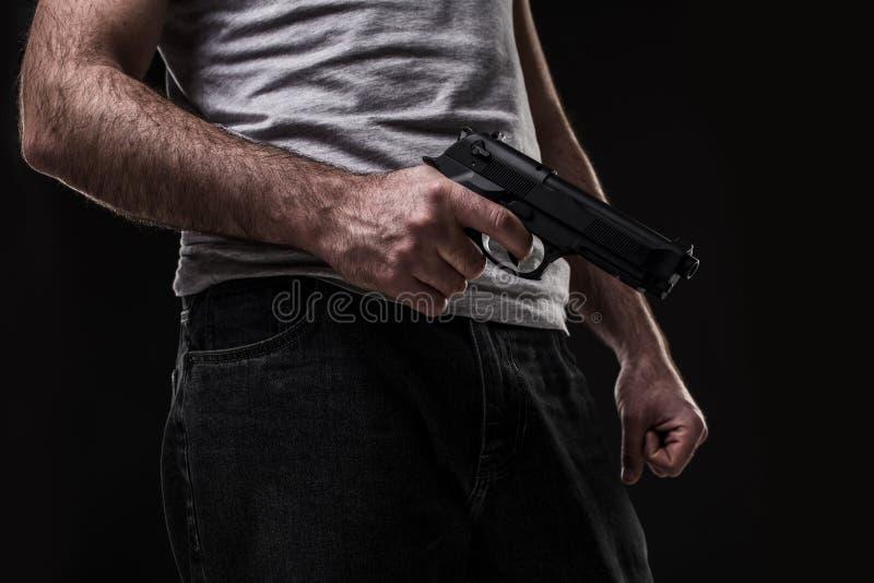 Убийца с оружием на черной предпосылке на студии стоковое изображение rf