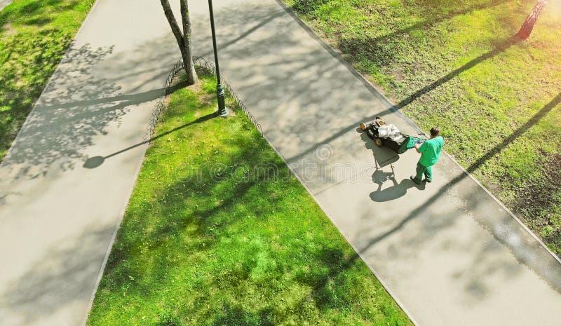 Уборка для районов парка Садовник с оборудованием привратника идет вдоль тротуара Вид с воздуха от трутня стоковые изображения rf