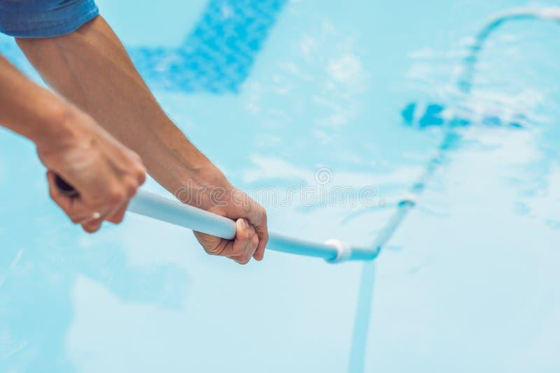 Уборщик бассейна Человек в голубой рубашке с оборудованием чистки для бассейнов, солнечным стоковые изображения