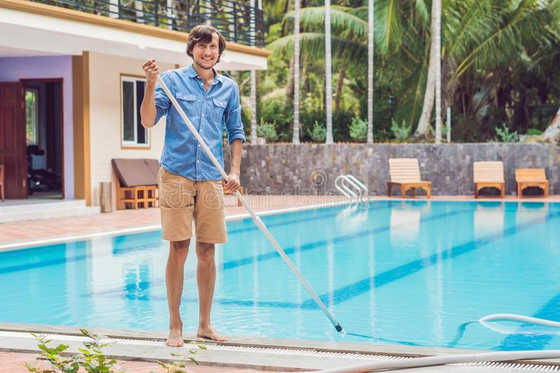 Уборщик бассейна Человек в голубой рубашке с оборудованием чистки для бассейнов, солнечным стоковое фото