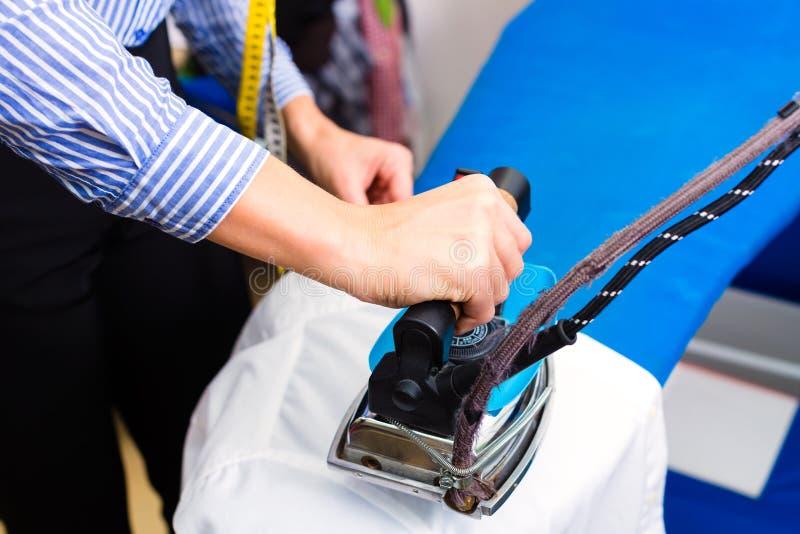 Уборщик в куртке магазина прачечной утюжа стоковое фото