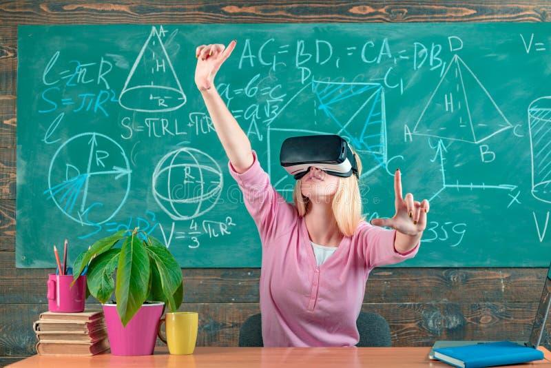 Увеличенная реальность Женщина в стеклах VR Уверенная женщина в шлемофоне виртуальной реальности указывая в воздух Современное об стоковое фото