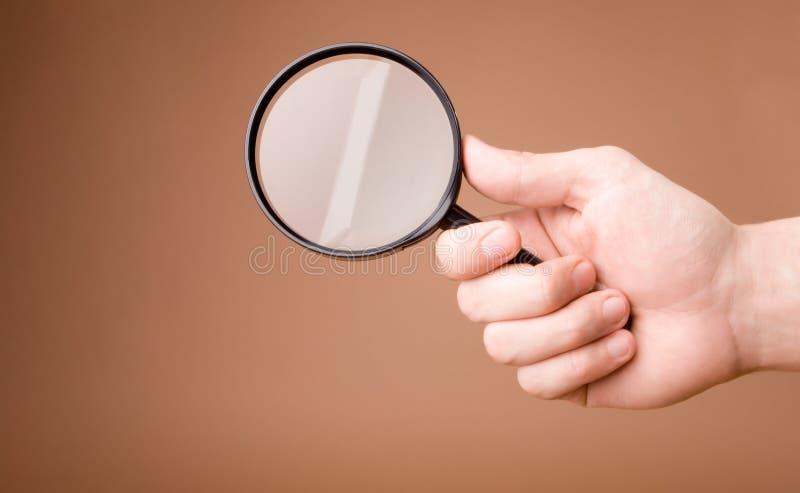 увеличивать удерживания руки предпосылки бежевый стеклянный стоковая фотография