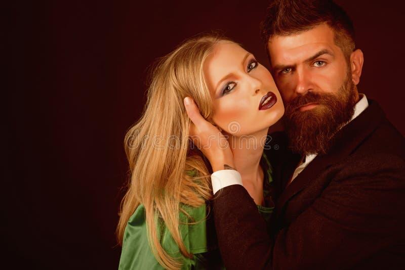 Увеличивая эмоциональная интимность Бородатая женщина объятия человека с длинными волосами Интимные пары в одежде моды женщина ти стоковое изображение