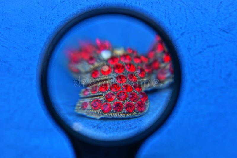 Увеличитель и старые золотые украшения с небольшими красными рубинами на голубой таблице стоковая фотография