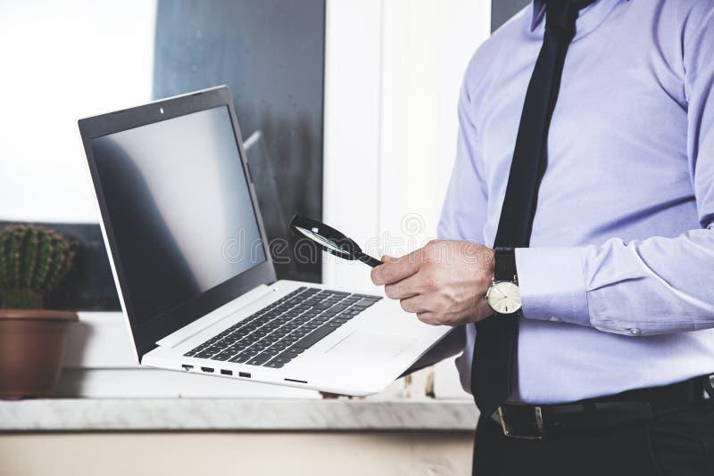 Увеличитель руки человека с компьютером стоковые фотографии rf