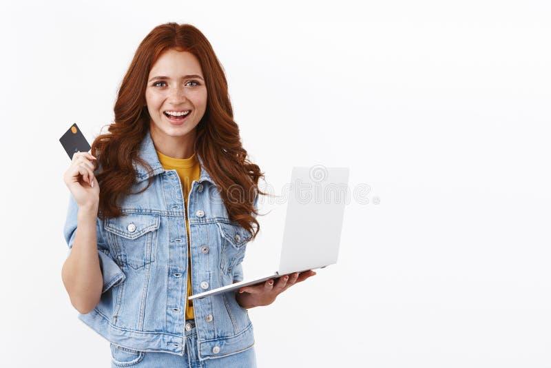 Уверенная беззаботная рыжевательная девушка с веснушками в джинсовой куртке, показывающая, как легко платить за товары онлайн, де стоковое изображение