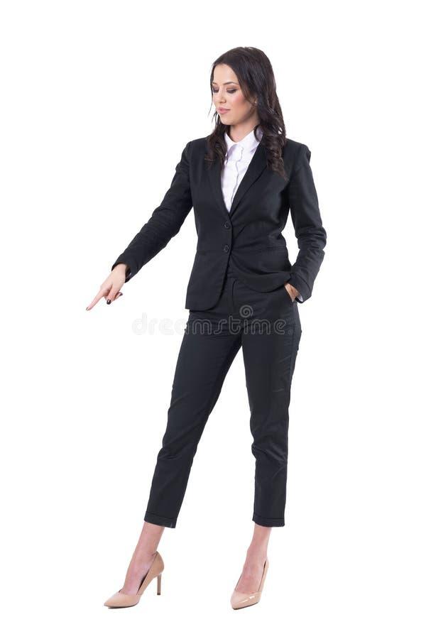 Уверенная бизнес-леди указывая палец вниз с показывать пустой космос экземпляра стоковые фото