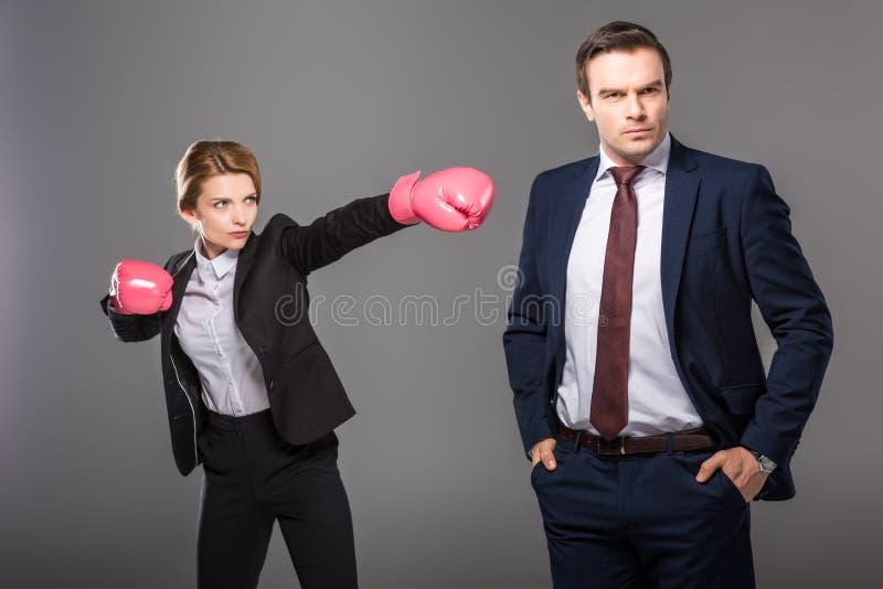 уверенная коммерсантка в перчатках бокса и красивый бизнесмен стоковое изображение rf