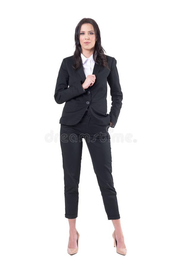 Уверенная коммерсантка в черном элегантном воротнике удерживания костюма представляя и смотря камеру стоковое изображение