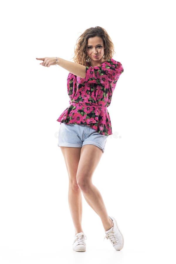 Уверенная улыбающаяся молодая женщина, глядя на камеру указывая пальцем вниз, отказываясь показывать двери стоковые фото