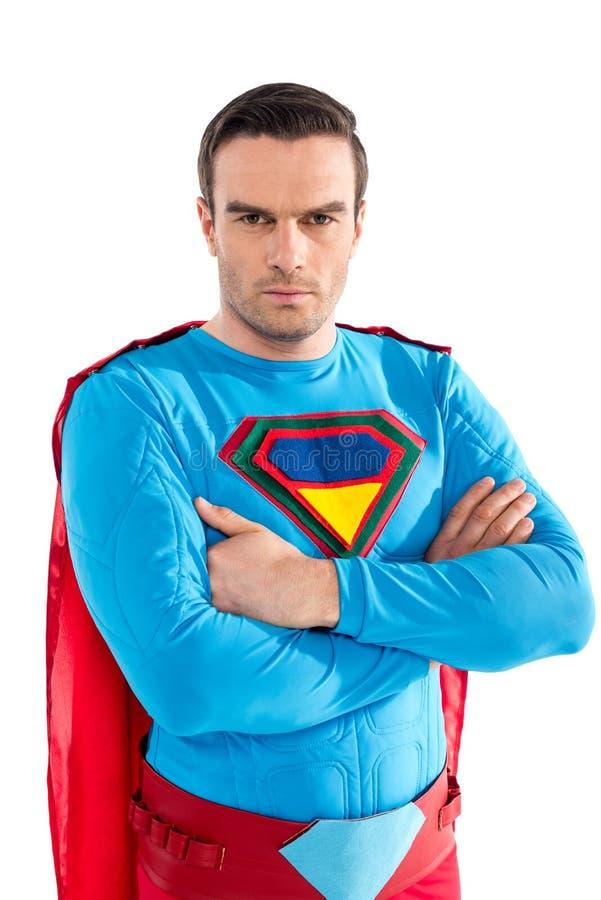 уверенное красивое положение супермена с пересеченными оружиями и смотреть камеру стоковые изображения rf
