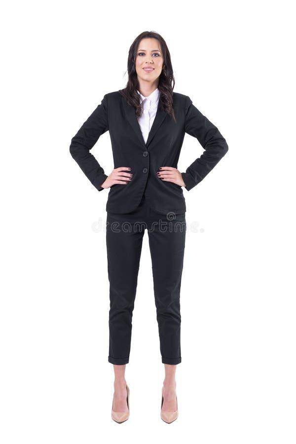 Уверенное положение женщины корпоративного бизнеса с оружиями на бедрах смотря камеру и усмехаться стоковые фото