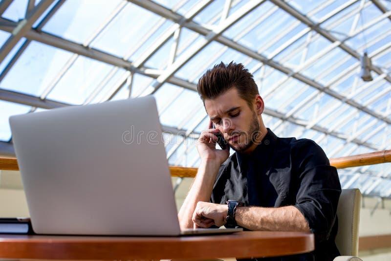 Уверенное руководство наблюдая на наручных часах и звонить по телефону стоковое фото