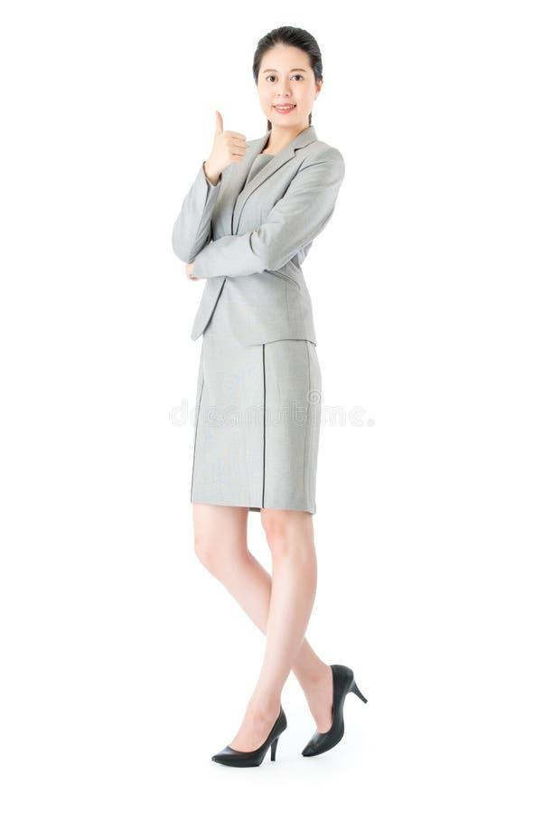 Уверенно азиатская бизнес-леди thumbs вверх по стоять стоковые фото