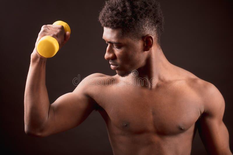 Уверенно африканская тренировка человека с желтой гантелью на черной предпосылке стоковое фото rf