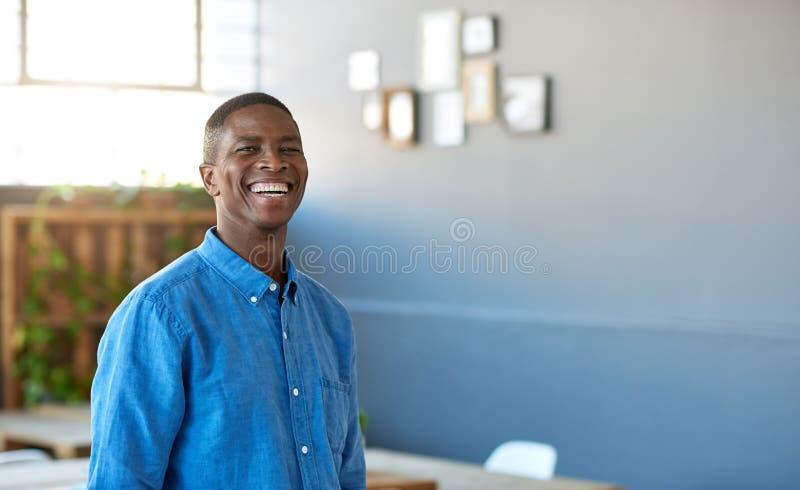 Уверенно африканский бизнесмен стоя в большой смеяться над офиса стоковые фото